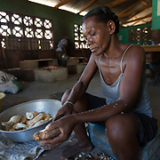 CAPTION: Oganizasyon Gwoupman Kominotè Pawas Sakrekè (OGKPS) is a community collective that has been working with IAF support to renovate and modernize its bakery and cassaverie (which processes manioc into flour and tapioca pancakes) in Laviolette, Cap-Haïtien. Here, Isabelle Saintilma is peeling cassava roots, the first stage in processing it. OGKPS started as a church movement, but has since become an entrepreneurial organization that welcomes people of all faiths, and emphasizes increased economic opportunities through trainings, livelihoods creation, and inclusion of women in decision-making processes.  ORGANIZATION: Organizasyon Gwoupman Kominotè Pawas Sakretè (OGKPS). LOCATION: #88 Laviolette (Monte Pa Desann), Cap-Haïtien, Haiti. INDIVIDUAL(S) PHOTOGRAPHED: Isabelle Saintilma.