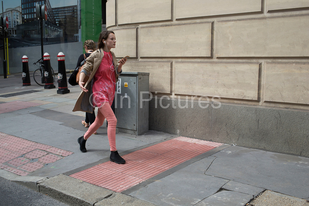 Woman walking along Upper Thames Street unawares that she is blending in with her surroundings wearing exactly the same colour trousers as the pavement in London, England, United Kingdom.