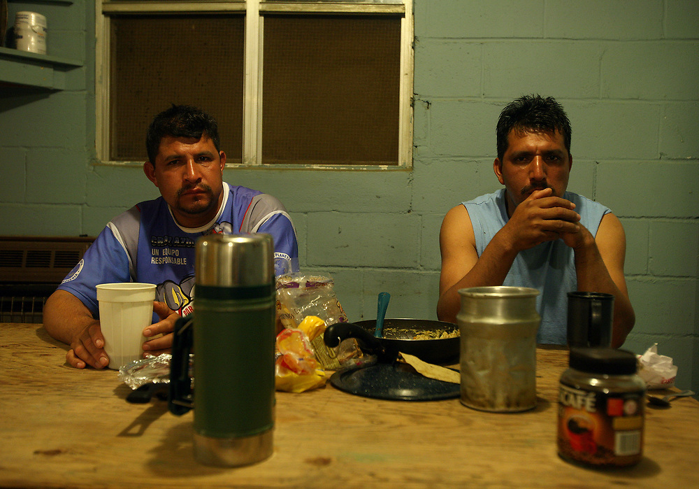 Brothers, Antonio, left, and Fransisco Yanes, 35, of Hidalgo, Mexico share a meal at their camp house dining area. Antonio is married, has two children, and has worked at Titan Farms for eight years. Fransisco is married, has 3 children, and has worked on the farm for 11 years.