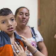 CAPTION: Nine-year-old Arnoldo Martinez was operated on in a hospital in San Pedro Sula, the largest city in Honduras, in order to repair his cleft lip. Since then, his family heard about Smile Train through the media. The doctors at Hospital Escuela will operate on the huge cleft palate within a week. LOCATION: Hospital Escuela, Tegucigalpa, Honduras. INDIVIDUAL(S) PHOTOGRAPHED: From left to right: Arnoldo Martinez Vargar, Norma Angelina Castellanel and Dr Gloria Baleska Caderes Estrada.
