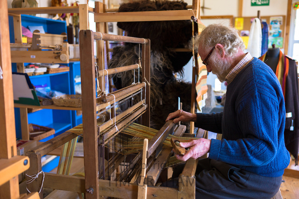 Craftsman using traditional loom to weave wool into handmade scarf at Croft Wools and Weavers, Applecross in the Highlands of Scotland