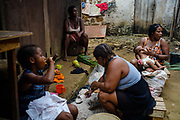 Women grating coconut while breast feeding at Roça Sundy, in Príncipe island