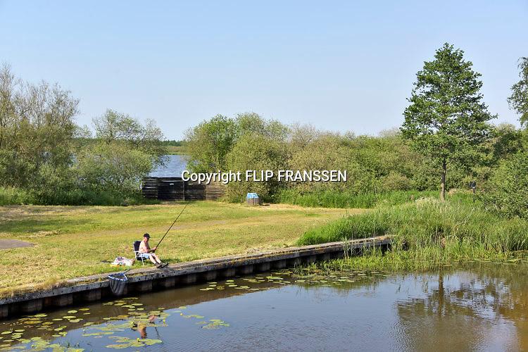 Nederland, Wolvega, 22-5-2018 Een oudere man, vist  in een waterplas en geniet op een rustig plekje van zijn oude dag. Foto: Flip Franssen
