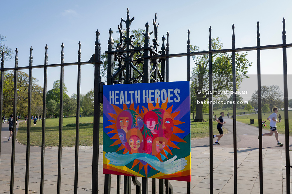 As the UK government's lockdown restrictions during the Coronavirus pandemic continues, and number of UK reported cases rose to 138,078 with a total now of 18,738 deaths, runnerss pass behind a home-made piece of art celebrating NHS (National Health Service) care worker heroes <br /> attached to the gates of Brockwell Park, a public green space in the south London borough of Lambeth, on 23rd April 2020, in London, England.