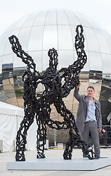 "© Licensed to London News Pictures. 08/06/2018. Bristol, UK. Bristol artist LUKE JERRAM stands by his new sculpture ""Inhale"", his newest piece which is unveiled this week for Bristol's Festival of Nature. Jerram's Inhale sculpture is designed to make the damaging effects of air pollution visible to everyone. It is three metres high and represents a diesel soot particle, actual size one micron but magnified 3 million times. The sculpture is made out of coal, with pyrite and calcite representing larger particles such as from vehicle disc brakes, and tiny bits of glitter representing tiny chemicals in diesel soot, some of which are thought to be carcinogenic. Jerram said the inspiration for the piece came from the recent Volkswagen diesel scandal and a friend whose child suffers from asthma. He chose diesel soot as the focus of the artwork as diesel vehicles are a significant contributor towards air pollution in the UK and in Bristol, air pollution is thought to contribute to five deaths a week. The sculpture is making its first public appearance as part of the Festival of Nature in Bristol on the weekend of June 9-10, and has been commissioned by the University of the West of England as part of its Our City Our Health project, which aims to draw attention to the health impacts of poorly designed cities. Photo credit: Simon Chapman/LNP"