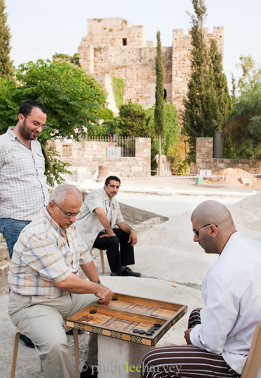 Men playing backgammon outside the ruins of Byblos Castle, built by crusaders in the small coastal town of Byblos, Lebanon