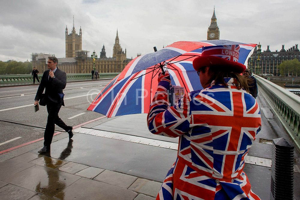 High winds and wet weather herald an uncertain week in the Britain less than 24 hours before the UK's general election. Unlikely prospects for a majority government by the end of the week means stormy deals between political parties and discontent with voters. As a businessman (or politician?) strides over the bridge, a tourist leaflet man dressed in union jacks hands out details for a nearby fish and chip business, opposite the Palace of Westminster, the symbol of the UK's parliamentary government, on the north side of Westminster Bridge.