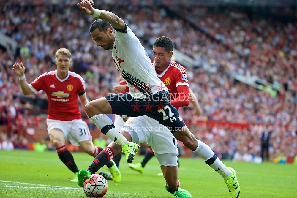MANCHESTER, ENGLAND - Saturday, August 8, 2015: Manchester United's Chris Smalling tackles Tottenham Hotspur's Nacer Chadli during the Premier League match at Old Trafford. (Pic by David Rawcliffe/Propaganda)