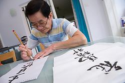 Man doing Chinese art writing using brush pen,