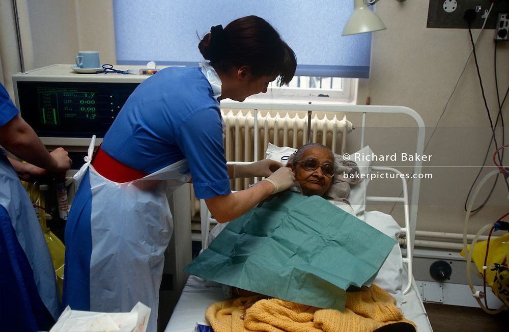 An elderly patient recovers after Hemodialysis blood purifying treatment in the Renal unit at St Bartholomews (Barts) Hospital in the City of London, England. The woman is laying back in an NHS bed being attended to by a nurse after spending some hours  with her right arm flat on a cushion and the tubes that feeds her blood by vascular access from her body into the dialyzer, a machine that filters the unpurified blood due to the patient's renal (kidney) failure. It is a bright room and many other machines are operating in this manner. Three quarters of the UK's 19,000 dialysis patients receive haemodialysis rather than Peritoneal dialysis, where a sterile solution containing minerals and glucose is run through a tube straight into the intestine.