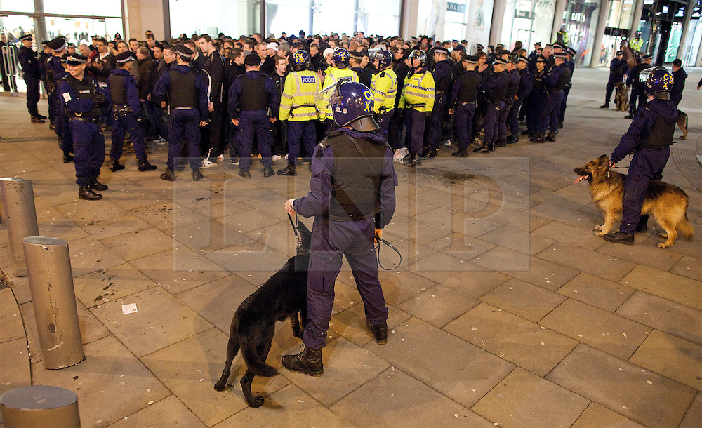 """© licensed to London News Pictures. Manchester, UK  23/02/2012. A large number of police contain about 150 Ajax fans. They lead them through Manchester and Salford to Old Trafford, closing many roads to traffic as they go. The crowd chant """"Amsterdam hooligans"""" as they go. This ahead of the Manchester United vs Ajax Europa League tie at Old Trafford. Photo credit should read Joel Goodman/LNP"""