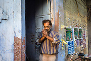 A man offering prayers on the street at dawn, Sitaram Bazar, Old Delhi, India