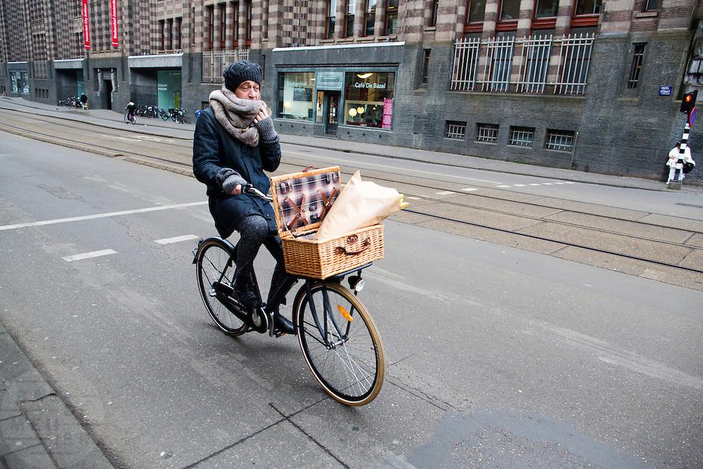In Amsterdam fietst een man met bloemen in het mandje voorop de fiets door de Vijzelstraat.<br /> <br /> In Amsterdam a man cycles with flowers in a basket at the Vijzelstraat.
