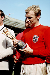 England captain Bobby Moore has a close look at the Jules Rimet trophy after his team's 4-2 win