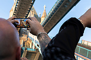Tourists taking photos with smart phones at Tower Bridge, London, England, UK