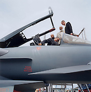 Visitors from a south Asian country admire British engineering and design at the BAE Systems stand where an open cockpit Typhoon fighter jet is on static display during the bi-annual aerospace industry expo at the Farnborough airshow in southern England. The Eurofighter Typhoon is a twin-engine, canard-delta wing, multirole fighter. The Typhoon was designed and is manufactured by a consortium of three companies; EADS, Alenia Aeronautica and BAE Systems, who conduct the majority of affairs dealing with the project through a joint holding company, Eurofighter Jagdflugzeug GmbH, which was formed in 1986. As an important trading partner, the controversial arms and weapons dealer BAE Systems helps to promote the UK-PLC  brand and urging foreign governments to buy British.