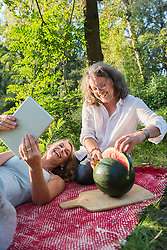 Couple on picnic using tablet and cutting watermelon, Bavaria, Germany