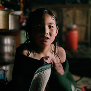 Sonam gets a wash, tomorrow is the first day of school. Life at Mr and Ms Wangchuk's house on the edge of the Laya village.