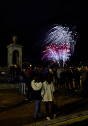 A crowd of people enjoying a fireworks display standing beside Pieroni's Fountain on Bog Island in the historic city of Bath.<br /> Bath, Avon, UK
