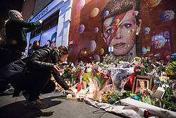 © Licensed to London News Pictures. 10/01/2017. London, UK. A woman lights a candle beneath a mural of David Bowie in Brixton, south London, to commemorate the first anniversary of the star's death. Photo credit: Rob Pinney/LNP