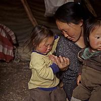 "MONGOLIA, Darhad Valley. Tsataan (""reindeer people"") mother and her children inside their tipi."