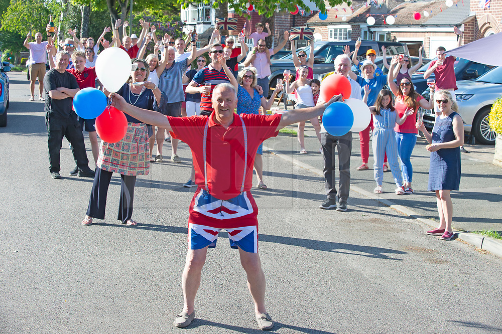 ©Licensed to London News Pictures 08/05/2020  <br /> Orpington, UK. 62 year old black cabbie Tony Boon holding balloons with his Broughton road neighbours from Orpington in the background.  VE-Day 75th anniversary celebrations in coronavirus lockdown. People enjoy parties in their front gardens with family and neighbours as they observe social distancing. Photo credit:Grant Falvey/LNP