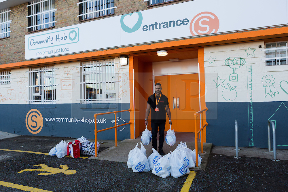 "© Licensed to London News Pictures. 19/12/2014. London, UK. A member of staff brings filled shopping bags for a customer ouside the Community Shop. The Community Shop opened this week in Gipsy Hill, South London and is a ""social supermarket"", which sells heavily-discounted surplus food that would otherwise be thrown away. Food is received from retail brands such as Marks & Spencer, Asda, Tesco, Innocent and Muller and many more. The shop works on a membership basis only, serving residents who are on income support and aimed at people who are in work, but low waged and for those working hard to find a job. Photo credit : Vickie Flores/LNP"