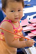 Asian toddler working at childrens craft table. Dragon Festival Lake Phalen Park St Paul Minnesota USA