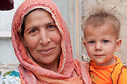 Afghanistan.Kabul , District 7, behind Technicom, Family outside their home. Mother and child.