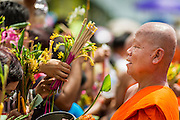 "12 JULY 2014 - PHRA PHUTTHABAT, SARABURI, THAILAND: Monks receive flowers the Buddhist faithful during the Tak Bat Dok Mai at Wat Phra Phutthabat in Saraburi province of Thailand. Wat Phra Phutthabat is famous for the way it marks the beginning of Vassa, the three-month annual retreat observed by Theravada monks and nuns. The temple is highly revered in Thailand because it houses a footstep of the Buddha. On the first day of Vassa (or Buddhist Lent) people come to the temple to ""make merit"" and present the monks there with dancing lady ginger flowers, which only bloom in the weeks leading up Vassa. They also present monks with candles and wash their feet. During Vassa, monks and nuns remain inside monasteries and temple grounds, devoting their time to intensive meditation and study. Laypeople support the monks by bringing food, candles and other offerings to temples. Laypeople also often observe Vassa by giving up something, such as smoking or eating meat. For this reason, westerners sometimes call Vassa ""Buddhist Lent.""    PHOTO BY JACK KURTZ"
