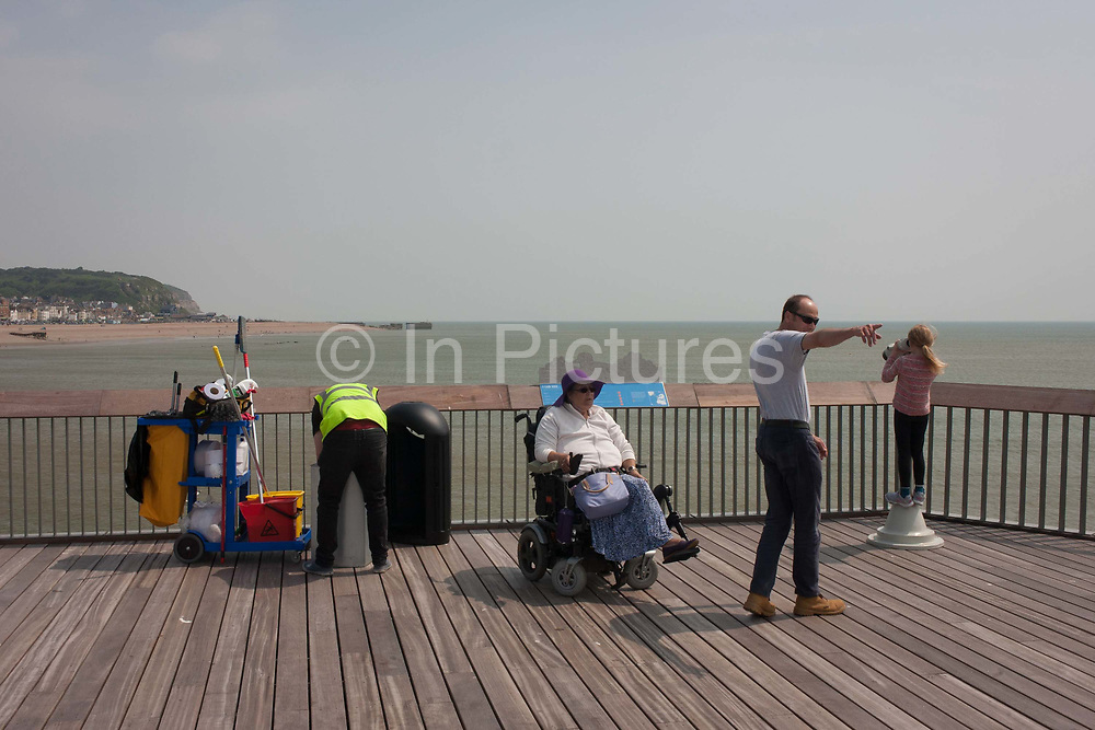 Closed after fire damage but recently re-opened, visitors enjoy the architecture and innovative design of the newly-opened Hastings pier in Sussex, England on 29th May 2016. Hastings Pier is a pleasure pier in Hastings, East Sussex, England. As a maintenance man empties bins, a disabled lady in a wheelchair enjoys the wide open spaces of decking which stretches out into the sea. Built in 1872 and enjoying its prime in the 1930s, though becoming a popular music venue in the 1960s, it received major storm damage in 1990 then in October 2010 it suffered a devastating fire the second in its history which destroyed 95% of its superstructure. In 2011, a total £8.75m grant was awarded by Heritage Lottery to rebuild the pier which was reopened to the public on 27 April 2016.