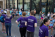 Charity supporters from Scope encourage participants taking part in the London Marathon on 22nd April 2018 in London, England, United Kingdom. The London Marathon, presently known through sponsorship as the Virgin Money London Marathon, is a long-distance running event. The event was first run in 1981 and has been held in the spring of every year since. The race is mainly known for ebing a public race where ordinary people can challenge themsleves while raising great amounts of money for various charities.