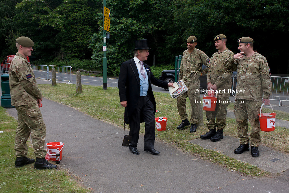 A formally-dressed gent walks past serving Coldstream Guards soldiers collecting cash for charity during the annual Royal Ascot horseracing festival in Berkshire, England. Royal Ascot is one of Europe's most famous race meetings, and dates back to 1711. Queen Elizabeth and various members of the British Royal Family attend. Held every June, it's one of the main dates on the English sporting calendar and summer social season. Over 300,000 people make the annual visit to Berkshire during Royal Ascot week, making this Europe's best-attended race meeting with over £3m prize money to be won.