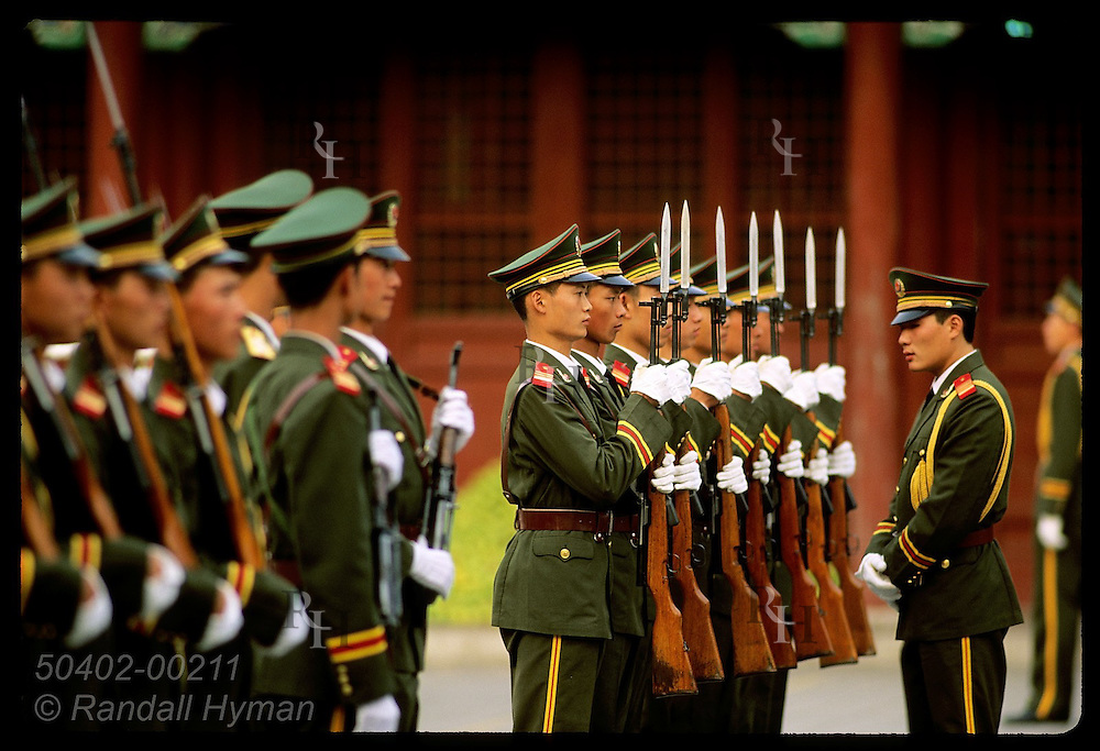 Officer inspects soldiers at attention during dress inspection outside Forbidden City; Beijing. China