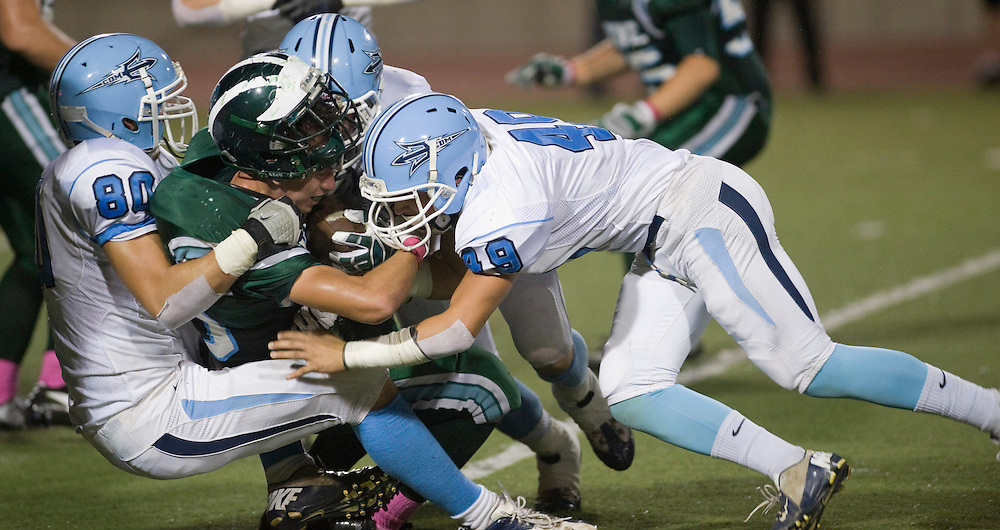 Irvine's Gary Renteria almost loses his helmet while being tackled by Corona del Mar's Justin Hess (80), Alexi Molinari and Robbie Hoffman (49) during Thursday's game.