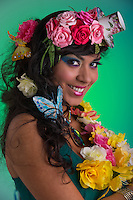 Portrait of smiley young woman with a floral wig looking at camera.