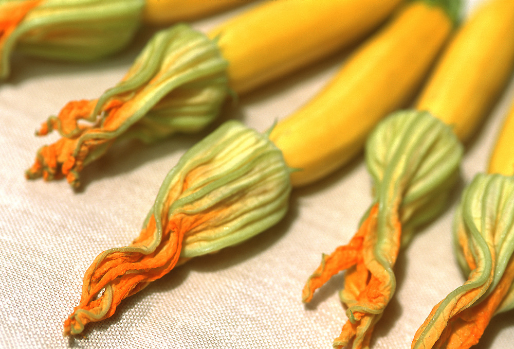 Close up selective focus photograph of a few Squash Blossoms on a tablecloth