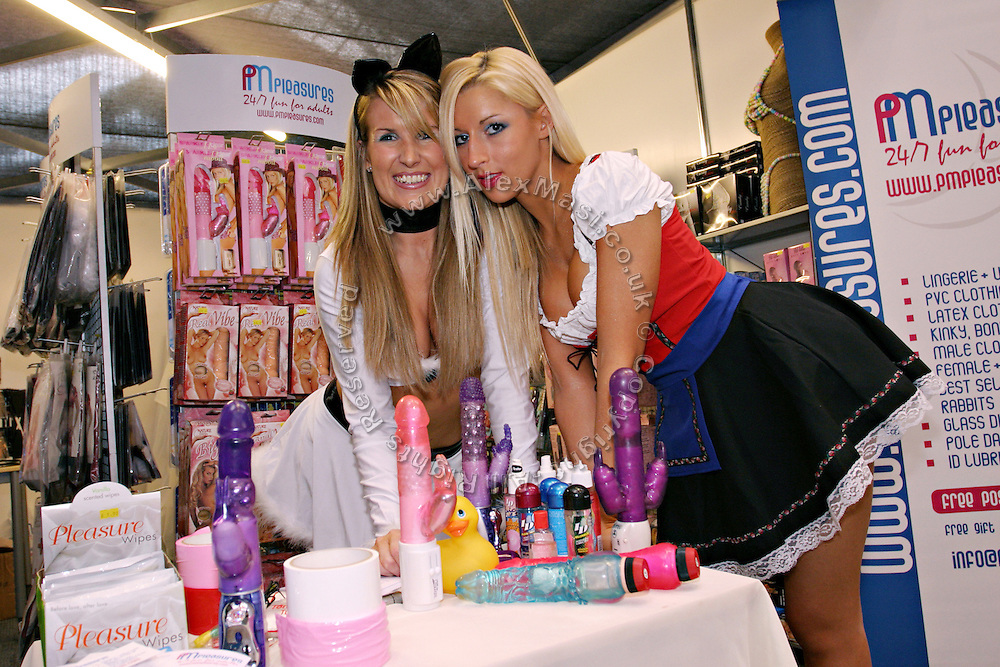 Two young women are posing by sex toys at one of the exhibitors' stands at the Erotica 2006 show in London, UK, on Friday, Nov. 17, 2006. Erotica is the world's largest adult lifestyle show. It attracts about 80,000 visitors every year with its over 150 retailer exhibitors, dazzling and decadent transvestite cabaret shows, fun foreplay seminars, beautiful lingerie collections, art and fetish demonstrations. **Italy Out**