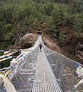 Trekker Liana Welty walks across a metal suspension footbridge spanning the Dudh Kosi river along the trail to Everest between Lukla and Namche Bazaar, Khumbu (Everest region), Himalaya Mountains, Nepal.