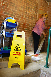 Cleaner mops the floor with health & safety warning sign in NHS building Yorkshire UK