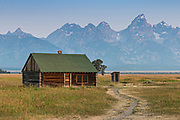 Morning sunrise over the Chambers homestead in the Mormon Row Historic District along Antelope Flats with the Grand Teton mountains behind at Grand Teton National Park, Wyoming.