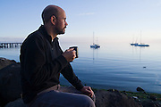 USGS landscape ecologist Christian Torgersen drinks tea outside his hotel room on the shore of Port Angeles Harbor, Washington. Torgersen was participating in the snorkey survey of the Elwha River.