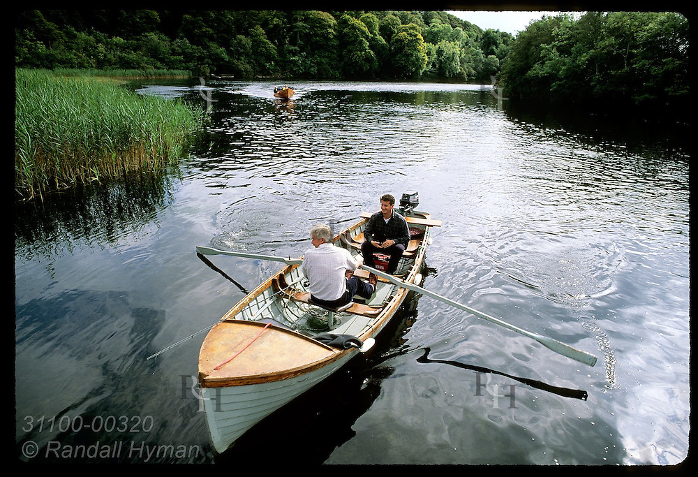 Guide rows guest final few feet to dock at Ashford Castle on Lough Corrib; Cong, Ireland.