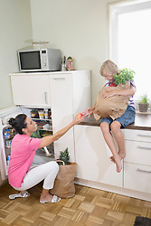 Woman giving an apple to her son at refrigerator, Bavaria, Germany