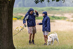 Licensed to London News Pictures. 06/08/202. London, UK. With weather more like September, walkers shelter from the rain in Richmond Park, southwest London as wind and rain is set to hit the South East today. Yellow weather warnings for England have been issued for heavy rain, flooding, and high winds as the bad weather is expected to continue throughout the weekend. However brighter weather is forecast for next week with highs of 22c. Photo credit: Alex Lentati/LNP