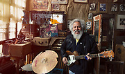 Happy older man playing guitar in his studio