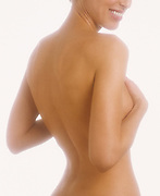 Rear view of nude woman with hands covering breasts and smiling