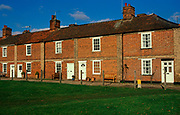 A753K8 Red brick terraced cottages on the village green, Mistley, near Manningtree, Essex, England