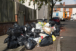© Licensed to London News Pictures. 14/09/2016. Birmingham, UK. As the bin men's strike continues in Birmingham. The Leader of the Council has resigned. The Council have taken on outside contractors to try to clear the mounting piles of rubbish. Pictured, Contractors trying to clear one of the worst affected roads, Medley Road in Sparkhill.  Photo credit: Dave Warren/LNP