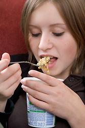 Portrait of  teenage girl eating a pot noodle,